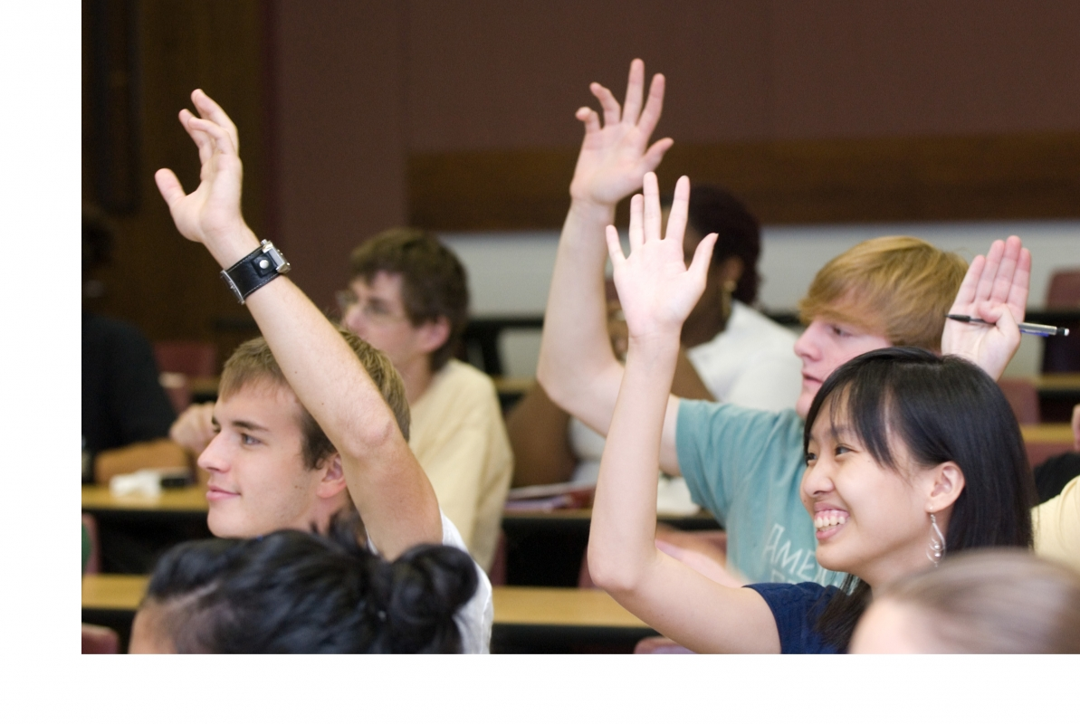 Multiple students raising their hands in a classroom setting